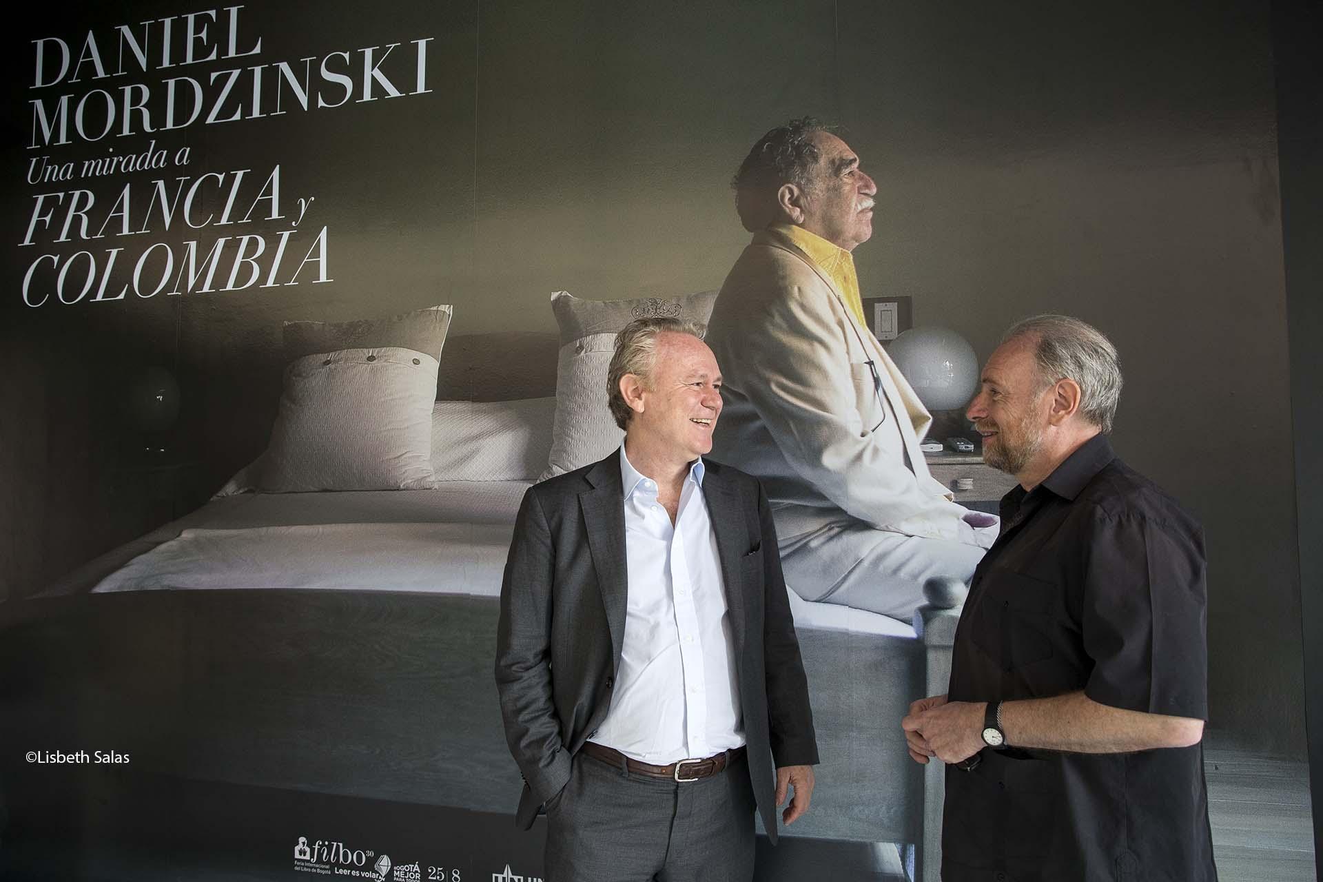 Mordzinski (derecha), con el editor y agente literario Cristóbal Pera, delante del retrato de García Márquez que anuncia la exposición.